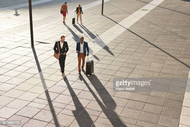 Businesspeople walking across square with rolling suitcases
