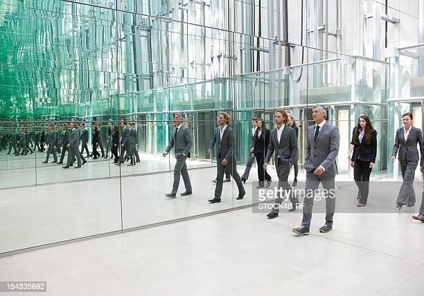 Businesspeople walking along mirror wall