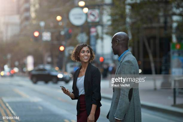 businesspeople walking and talking on avenue of san francisco - gray coat stock pictures, royalty-free photos & images