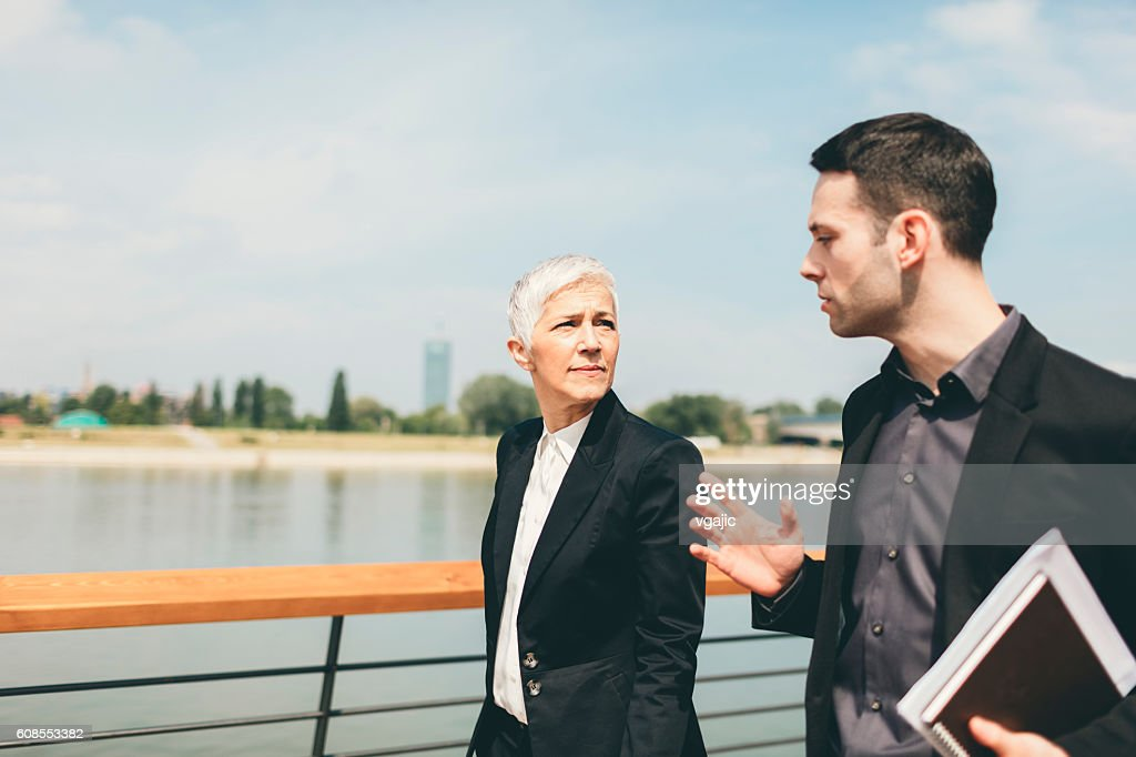 Businesspeople Walking and Talking Outdoors. : Stock Photo