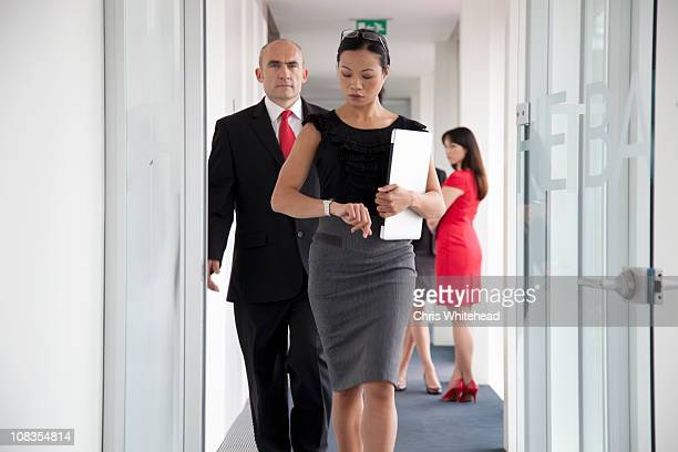 Businesspeople walking down corridor