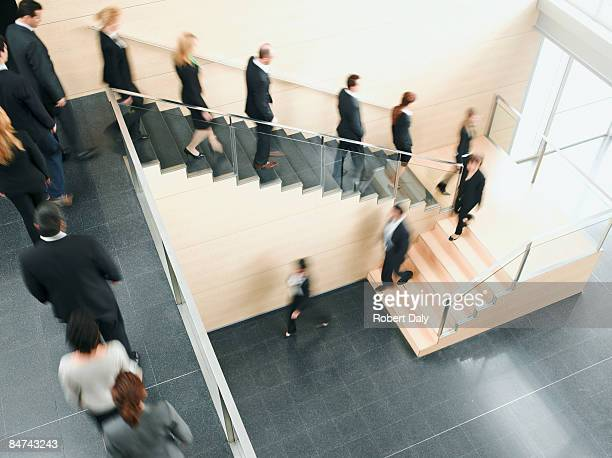businesspeople walking down office staircase - downsizing unemployment stock pictures, royalty-free photos & images