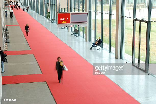 businesspeople walking in a convention center - tradeshow stock pictures, royalty-free photos & images