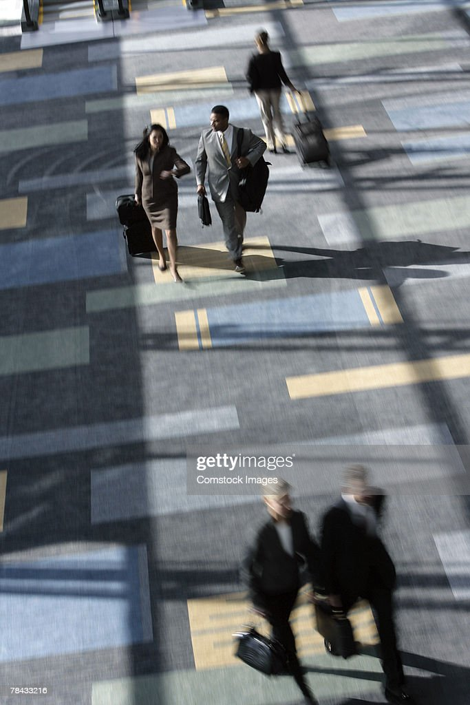 Businesspeople walking in airport : Stockfoto