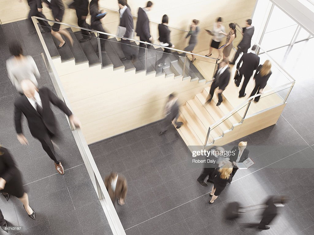 Businesspeople walking in busy office building : Stock Photo