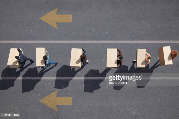 Businesspeople walking in lane with painted arrows, carrying moving boxes
