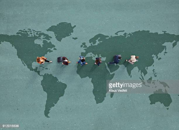 businesspeople walking in line across world map, painted on asphalt - globale kommunikation stock-fotos und bilder