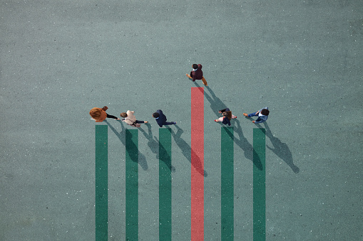 Businesspeople walking in line on bar chart painted on asphalt, one person walking off. - gettyimageskorea