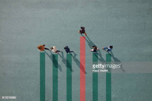 businesspeople walking in line on bar chart painted on asphalt, one person walking off. - individualiteit stockfoto's en -beelden