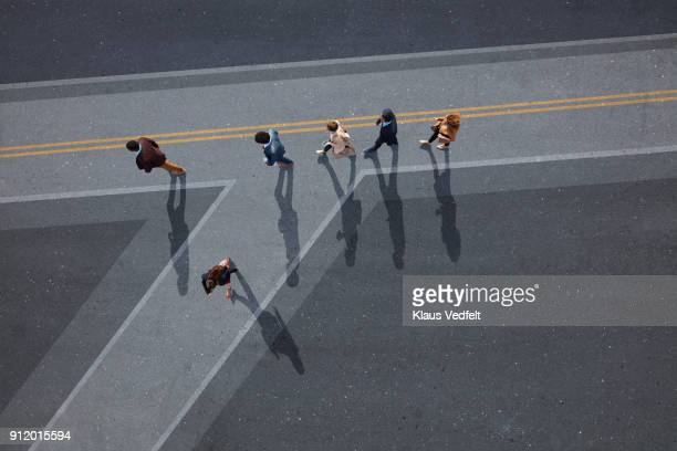 Businesspeople walking in line on road, painted on asphalt, one person walking off in different direction