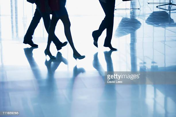 Businesspeople walking in lobby, low section