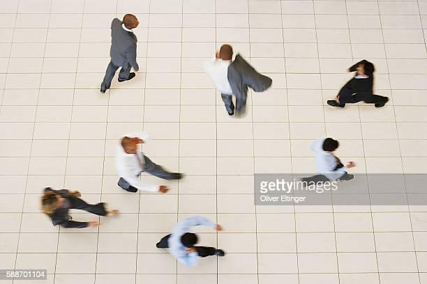 businesspeople walking in lobby - oliver eltinger stock-fotos und bilder