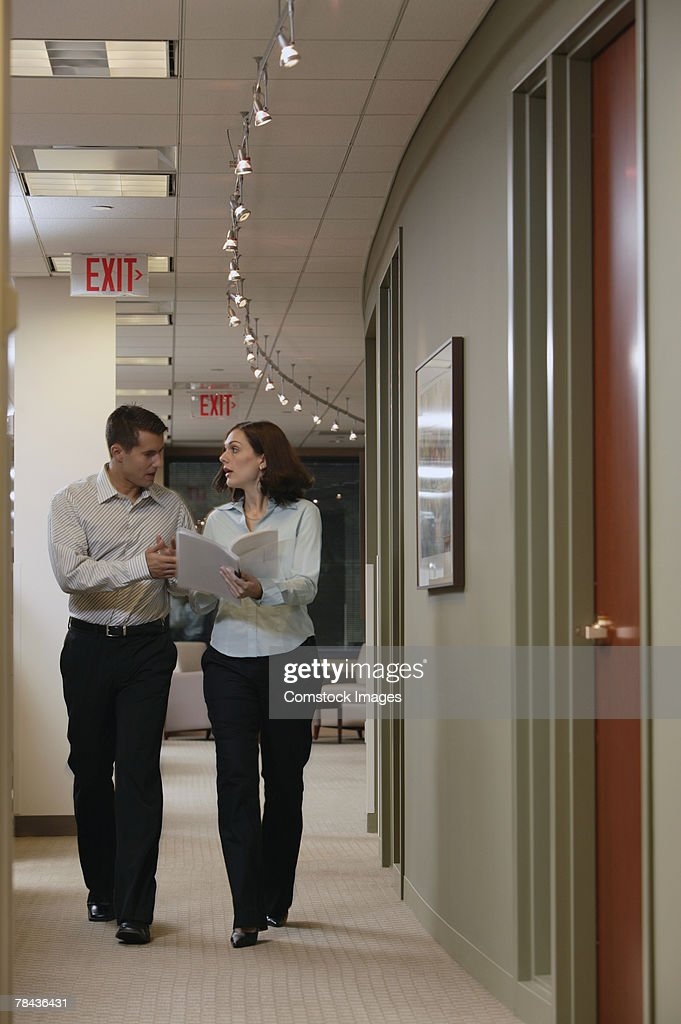 Businesspeople walking in office hallway : Stockfoto