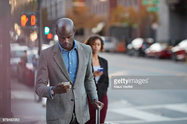 Businesspeople walking in pedestrian crossing and checking smartphones