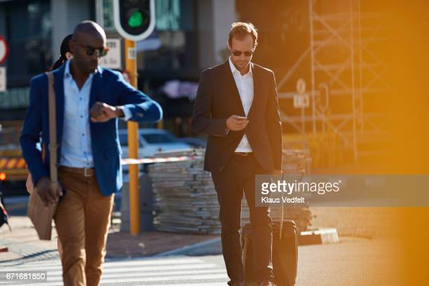 businesspeople walking in pedestrian crossing with phones and bags - pedestrian stock pictures, royalty-free photos & images
