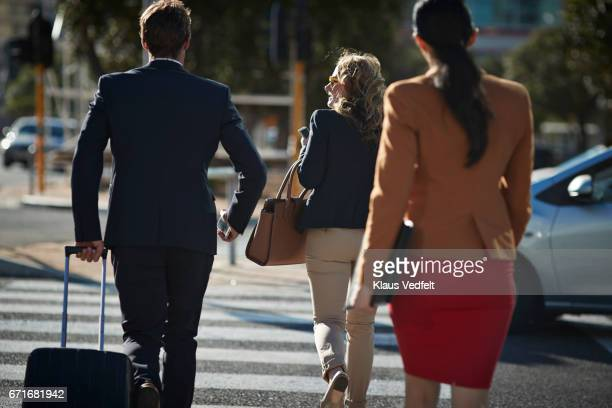 Businesspeople walking in pedestrian crossing with phones and bags