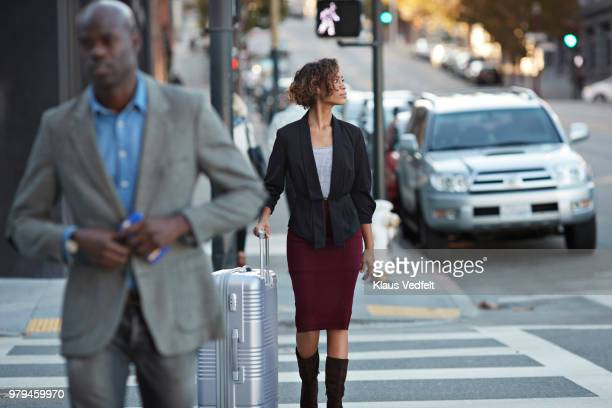 Businesspeople walking in pedestrian crossing, woman with rolling suitcase