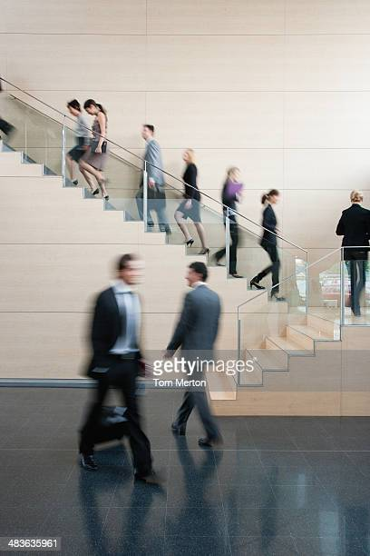businesspeople walking on busy office staircase - medium group of people stock pictures, royalty-free photos & images