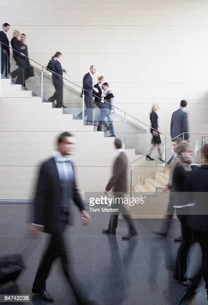 Geschäftsleute gehen auf geschäftigen Büro-Treppe