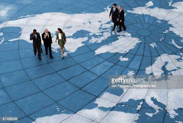 Businesspeople walking on map of globe