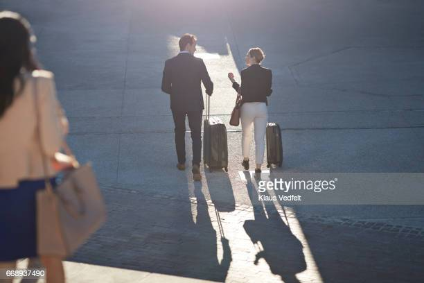 Businesspeople walking on outside staircase with bags