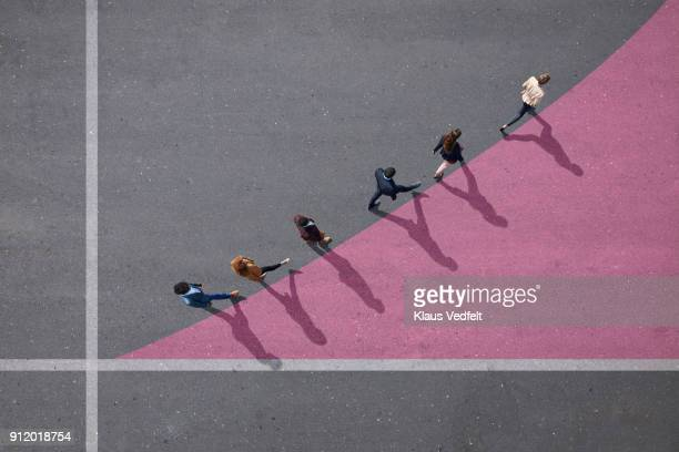 businesspeople walking on painted up going graph, on asphalt - zusammenhalt stock-fotos und bilder