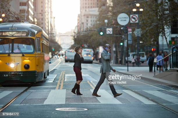 Businesspeople walking on pedestrian crossing, while talking on smartphone