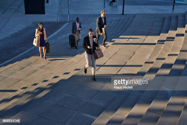 Businesspeople walking on staircase outside