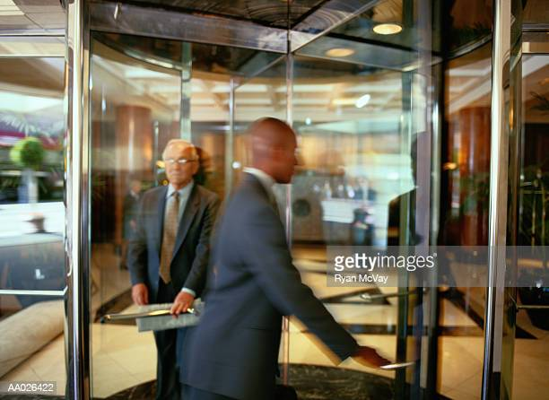 businesspeople walking through a revolving door - revolve stock photos and pictures
