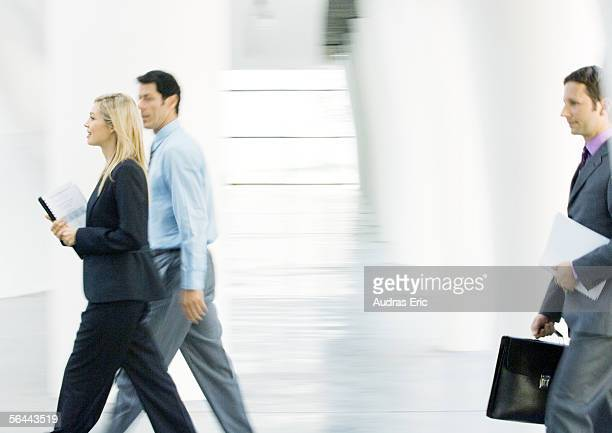 businesspeople walking through lobby - moving past stock photos and pictures