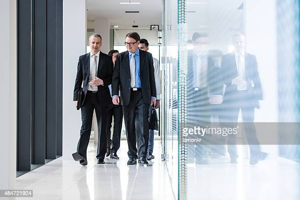 Businesspeople walking through office corridor
