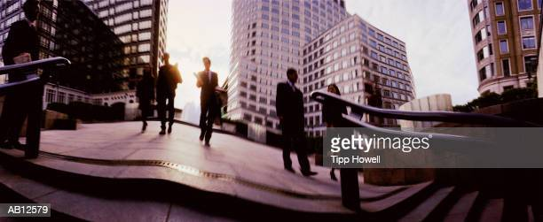 Businesspeople walking through square (wide angle)