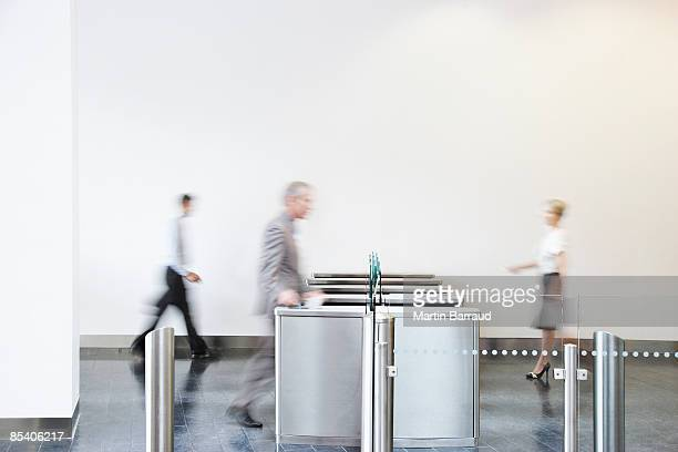 businesspeople walking through turnstile - aankomst stockfoto's en -beelden