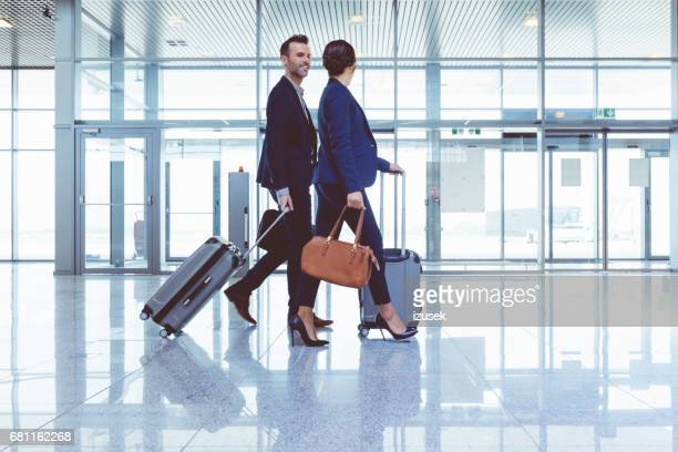 Businesspeople walking with luggage inside airport terminal