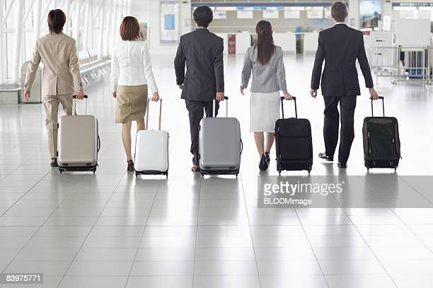 businesspeople walking with suitcases, rear view - endast vuxna bildbanksfoton och bilder
