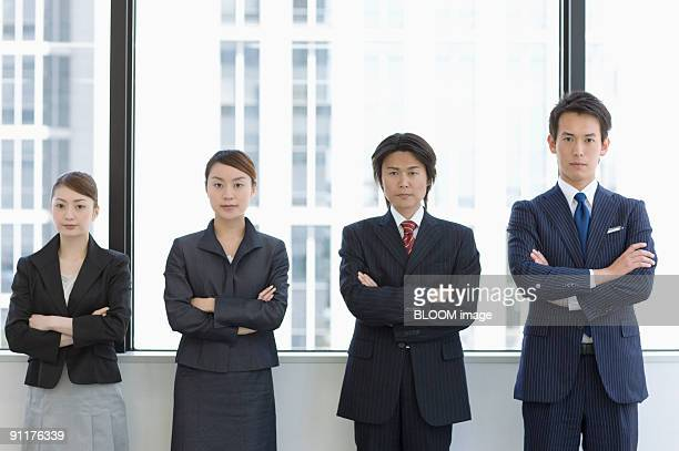 Businesspeople with arms folded, portrait