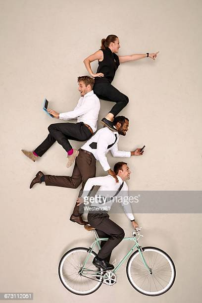 Businesspeople with bicycle on top of each other working on mobile devices