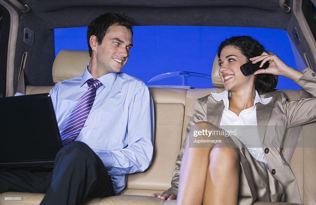 Businesspeople with laptop in backseat : Stock Photo