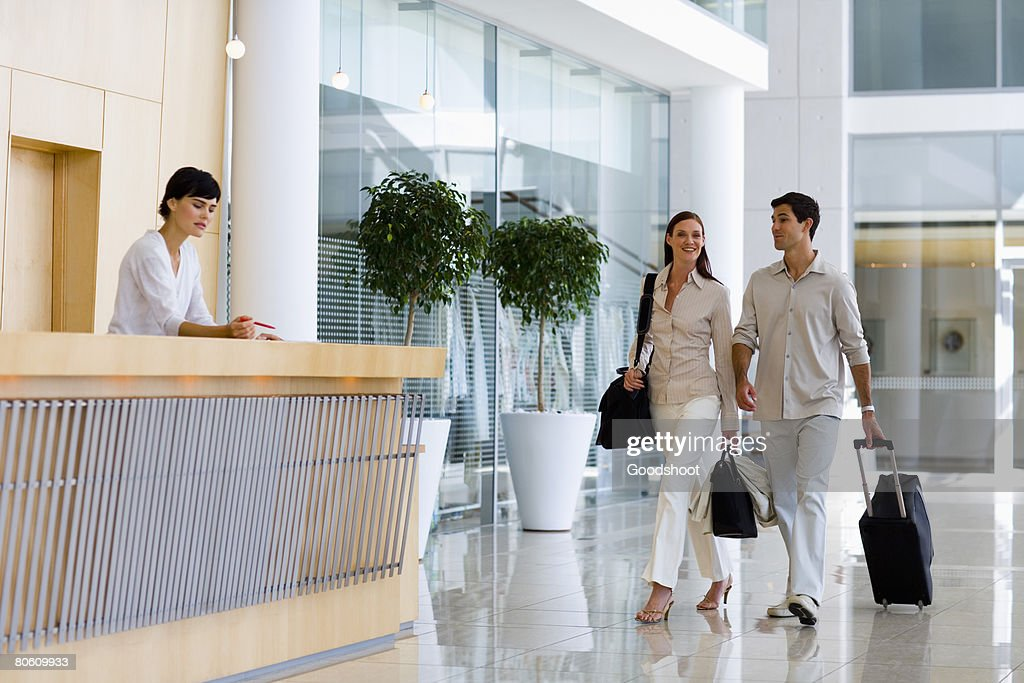Businesspeople with luggage at hotel : Stock Photo