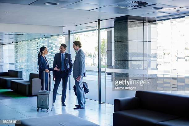 businesspeople with luggage discussing at lobby - business travel stock pictures, royalty-free photos & images