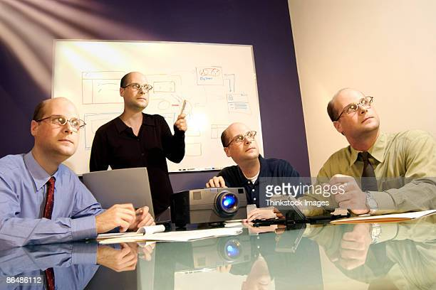 businesspeople with same head watching presentation - cloning stock pictures, royalty-free photos & images