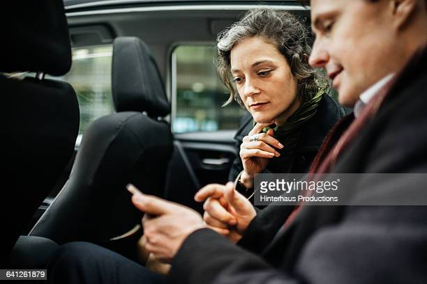Businesspeople with smart phone in a taxi