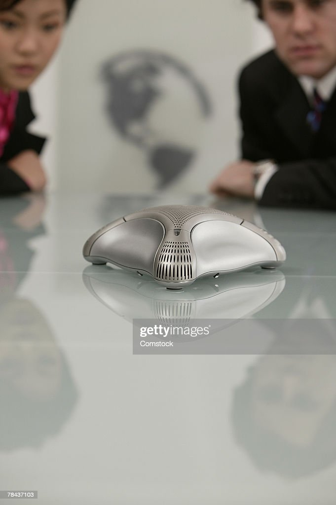 Businesspeople with teleconference machine : Stockfoto