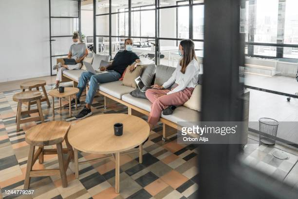 businesspeople working and maintaining social distance on a sofa in a modern office - new normal concept stock pictures, royalty-free photos & images