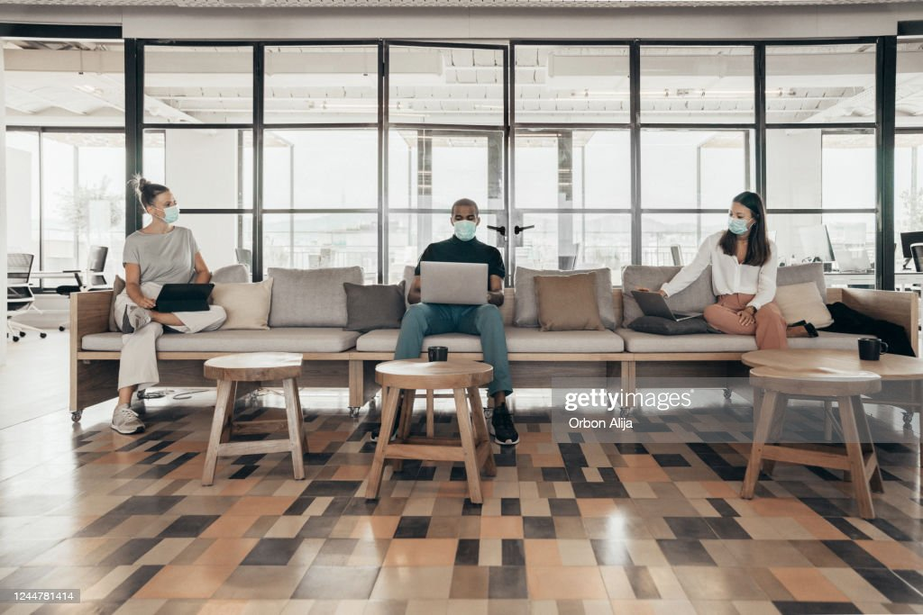Businesspeople working and maintaining social distance on a sofa in a modern office : Stock Photo