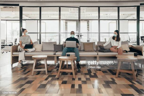 businesspeople working and maintaining social distance on a sofa in a modern office - social distancing stock pictures, royalty-free photos & images