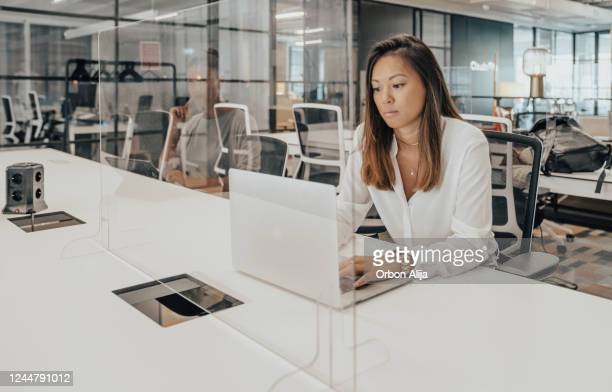 businesspeople working at office with glass partition dividing them - prevention stock pictures, royalty-free photos & images