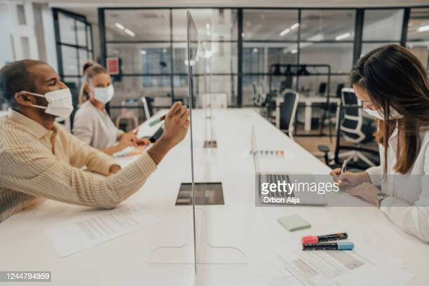 empresários que trabalham no escritório com partição de vidro dividindo-os - grupo pequeno de pessoas - fotografias e filmes do acervo
