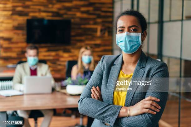 businesspeople working with face masks in the office during covid-19 pandemic - illness prevention stock pictures, royalty-free photos & images