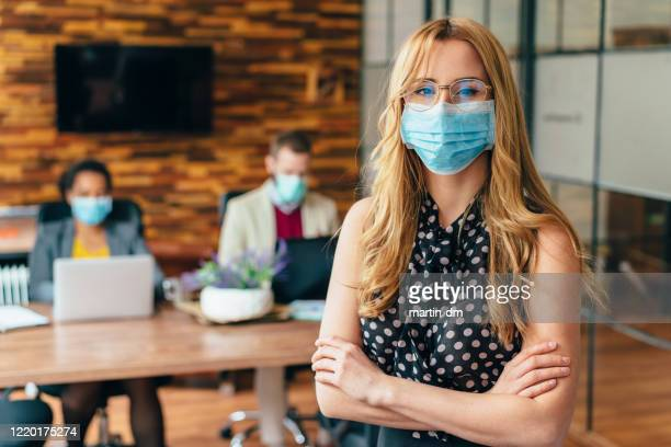 businesspeople working with face masks in the office during covid-19 pandemic - prevention imagens e fotografias de stock